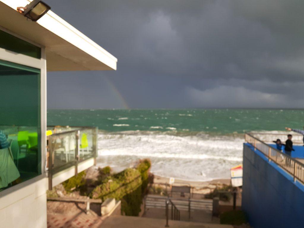 sunshine through dark clouds on Cottesloe Beach